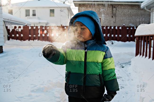 Boy standing on the snowy street and watching his visible breath