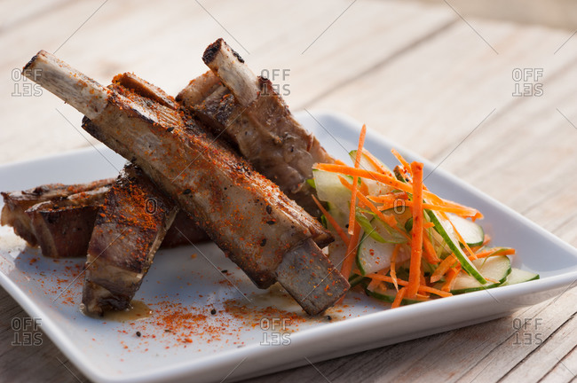 Pork ribs served with shredded carrot and sliced cucumber