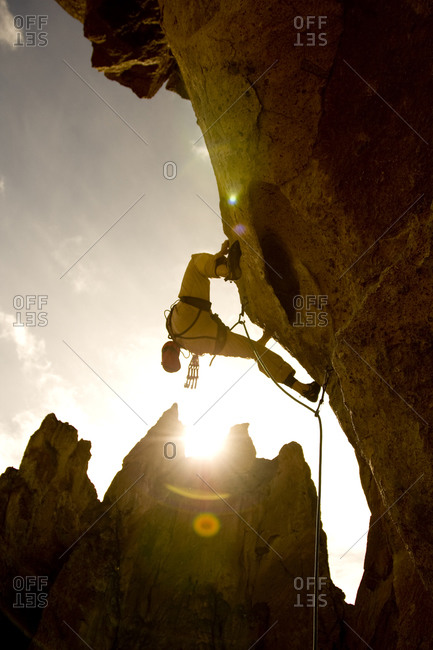 A rock climber on a rocky face backlit by the setting sun