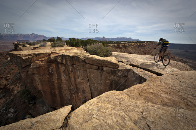 A man mountain biking next to a steep cliff near Hurricane Utah.