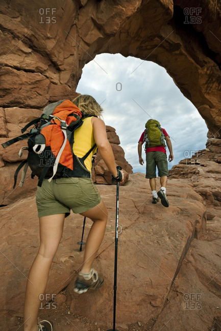 A man and woman hiking up to an arch in Arches National Park Utah.