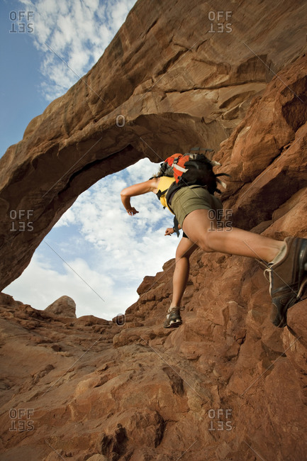 A woman jumps across rocks below an arch in Arches National Park Utah.