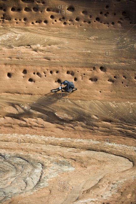Man mountain biking on vertical wall in Moab Utah.