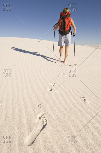 A woman hiking across sand dunes.