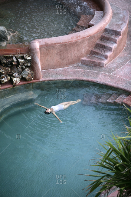 A beautiful woman floats in a large saltwater pool in Zihuatanejo Mexico.