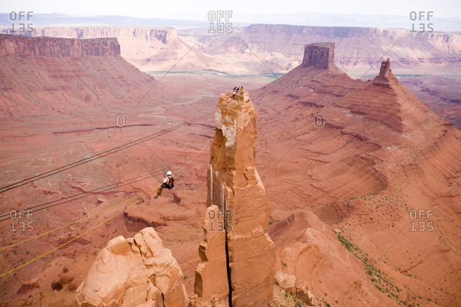 Adventure racer on a Tyrolean Traverse high above the desert in a race in Moab Utah.