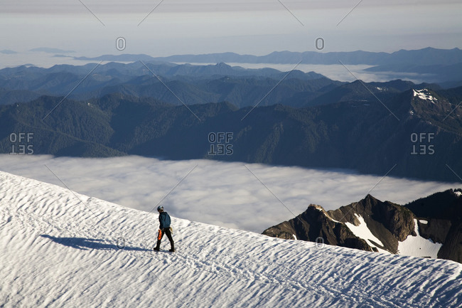 A climber walks towards a snowy summit in Olympic National Park WA.