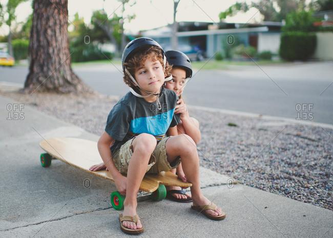 Children sitting on skateboard