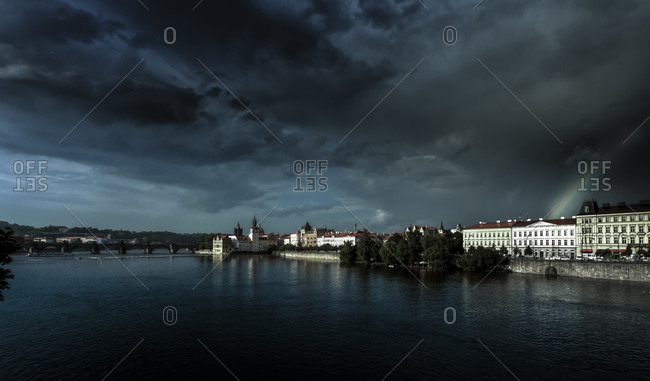 Cityscape with Vltava with thunderclouds