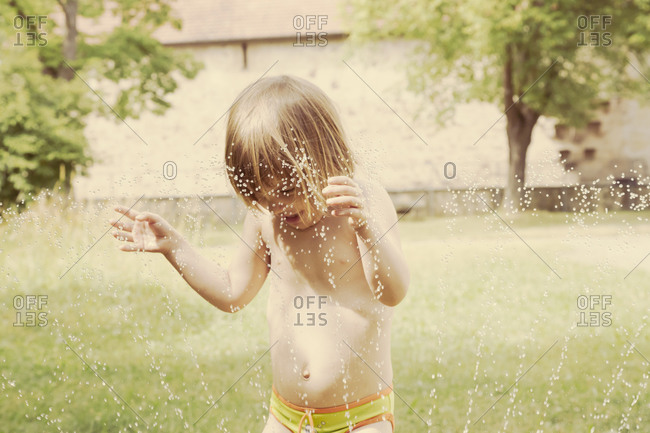 Portrait of little girl having fun with lawn sprinkler in the garten