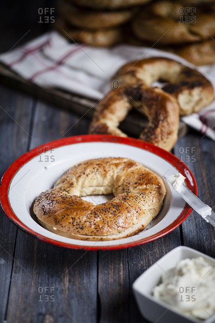 Plate of home-baked bagel and bowl of cream cheese