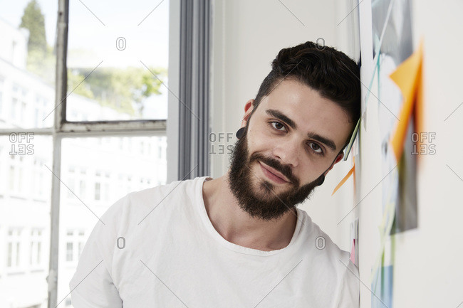 Smiling man leaning against wall with adhesive notes