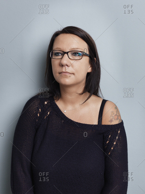 Portrait of brunette woman with glasses in front of gray background
