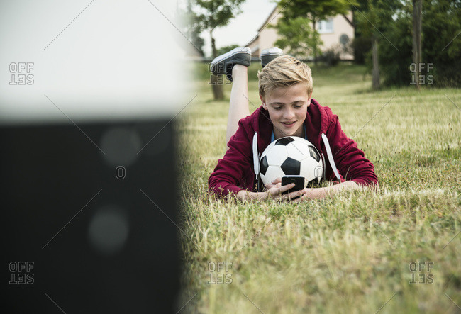 Teenage boy with soccer ball, using smartphone