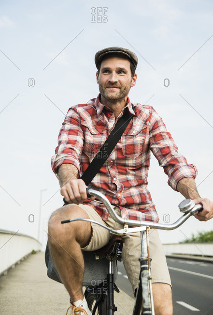 Man with cap riding a bicycle