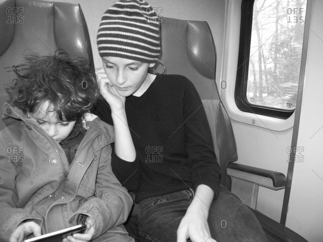 Brother and sister watching tablet on a train