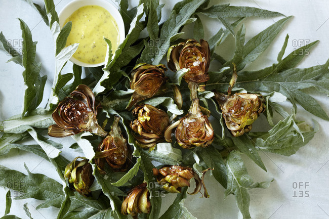 Top view of halved roasted artichokes with cannabis dressing