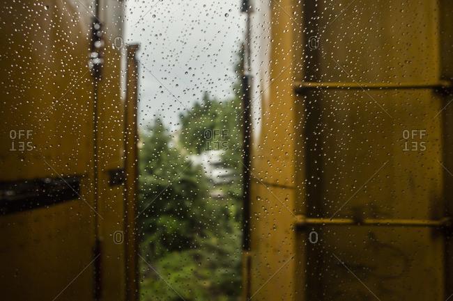 View of an opened door through a wet window