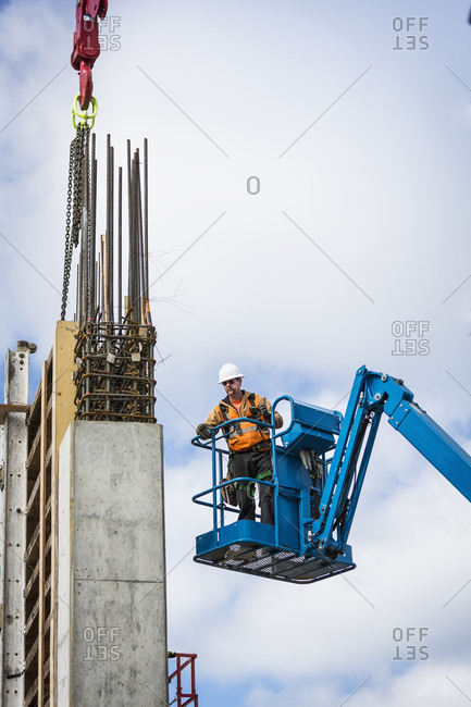 Caucasian worker standing on boom lift on site