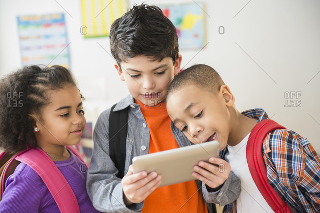 Students using digital tablet in classroom