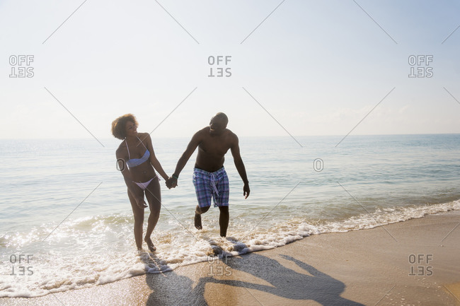 Couple holding hands in waves on beach