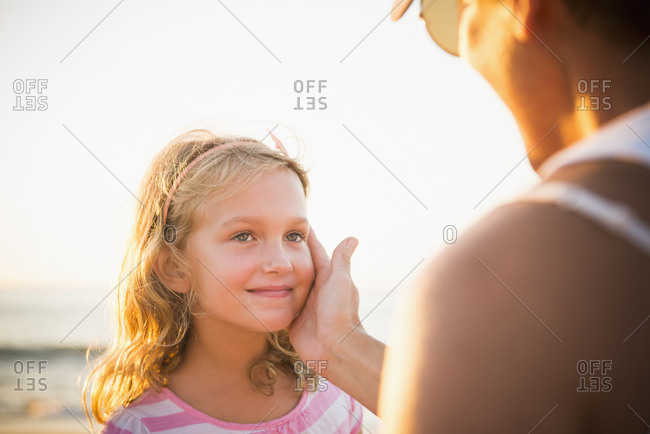 Mother cupping daughter's face on beach