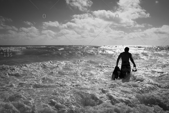 Man wading into the ocean