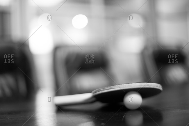 A ping pong racket leaning on a ping pong ball