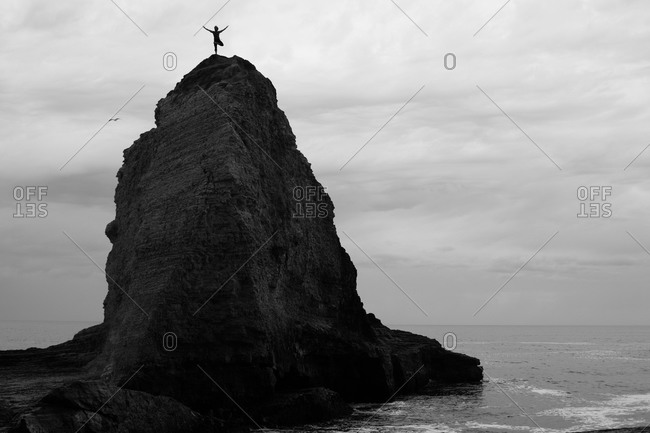 Person standing on top of a rock on Panther beach, Santa Cruz, USA