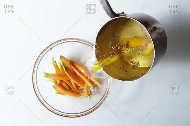 Pouring preserving liquid over fresh baby carrots