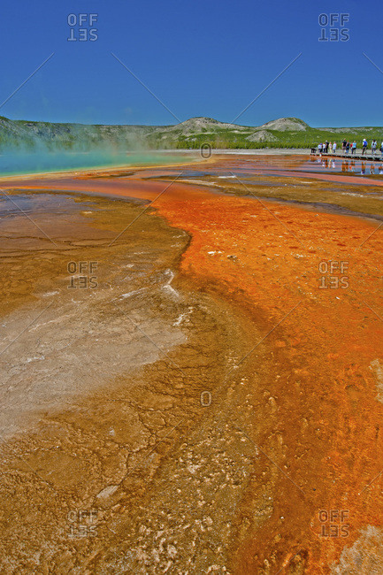 Tourists hike on a boardwalk beside Grand Prismatic Spring.
