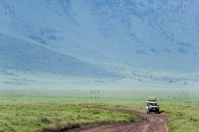 A safari vehicle crosses the savannah plain on the floor of a volcano caldera.