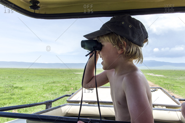A small boy searches for wildlife on the vast savannah plain with binoculars.