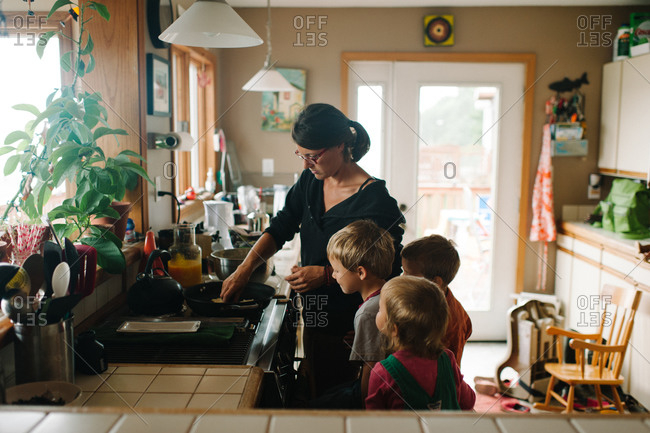 Woman cooking with children in a kitchen