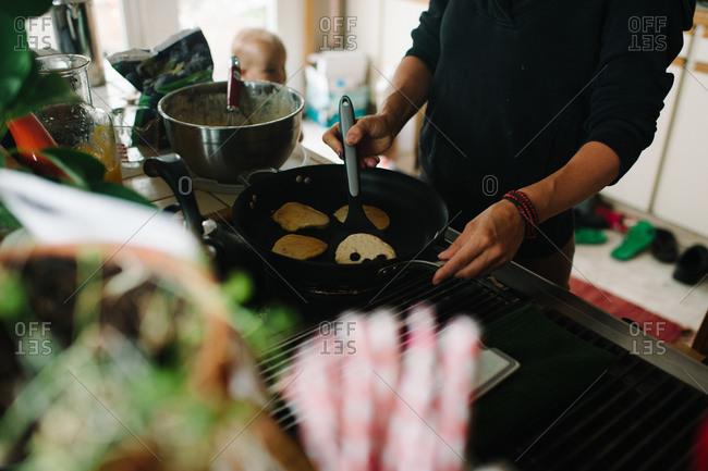 Woman making pancakes in a kitchen