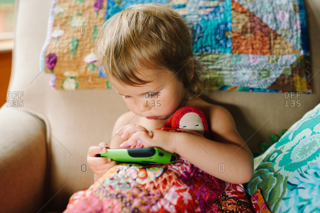 Little girl playing on tablet and holding her toy