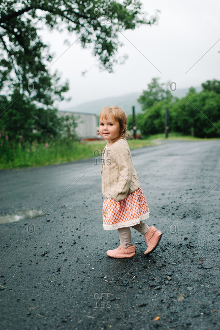 Little girl takes a walk on a wet road