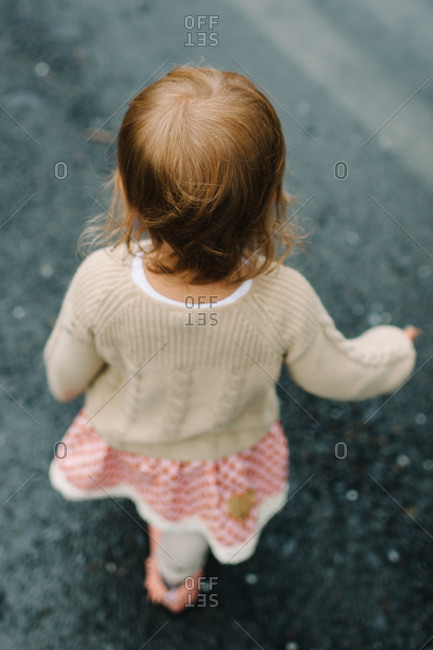 Overhead view of little girl walking on wet road