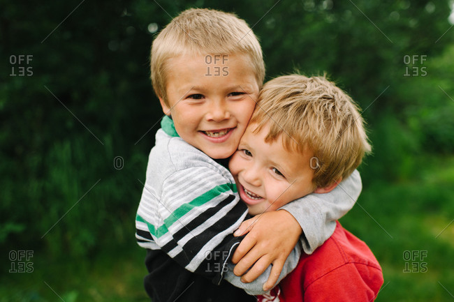 Older brother holding tight his younger brother