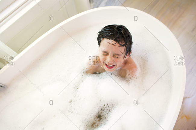 Young boy in sudsy bath water