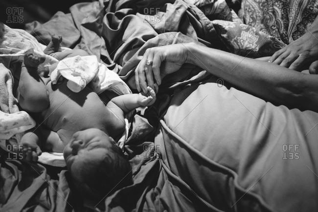 Woman holding a newborn baby's hand