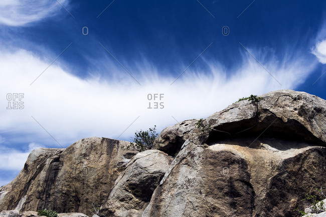 Wispy clouds crowning a rocky granite outcrop on the savannah known as a kopje.
