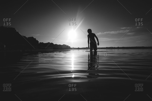 Silhouette of a boy standing in the water at sunset
