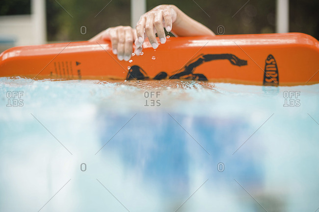 Child with a swimming float in a pool