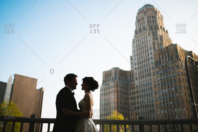 Buffalo City Hall behind embracing newlyweds, Buffalo, New York