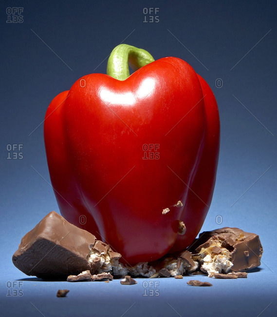 Red bell pepper smashing a chocolate bar