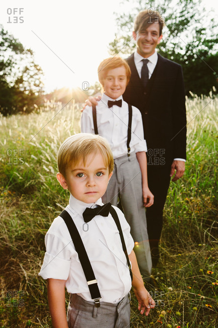 Father and his sons posing outdoors stock photo - OFFSET