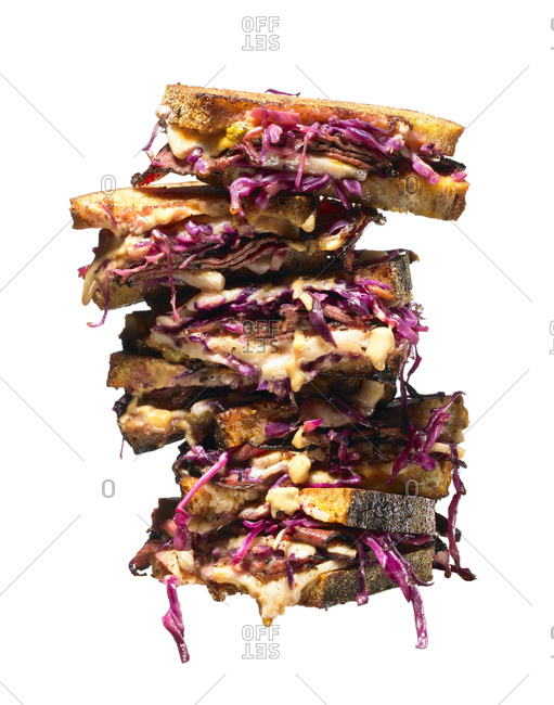 Stacked pastrami sandwiches over white background