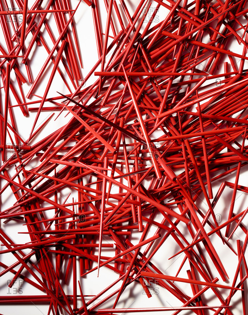 Red chopsticks scattered over white background