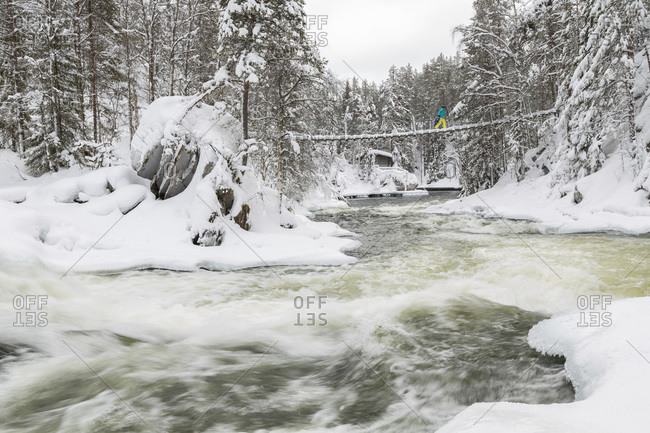 Person crossing a bridge above the Myllykoski rapids in Oulankajoki National Park, Finland